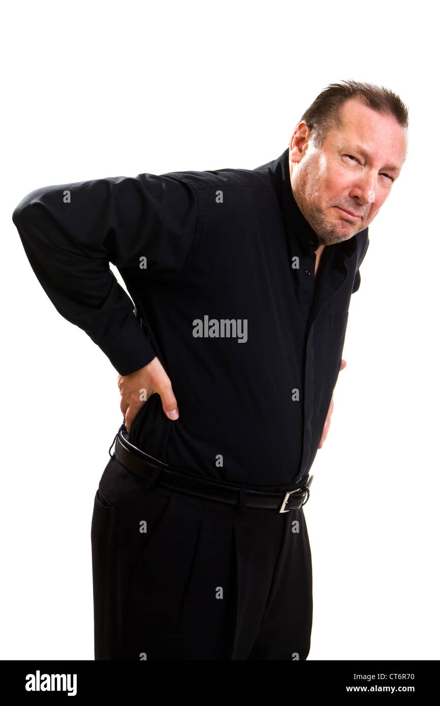 Elderly man holds his back and bends over in pain and makes a grimacing facial expression. - Stock Image