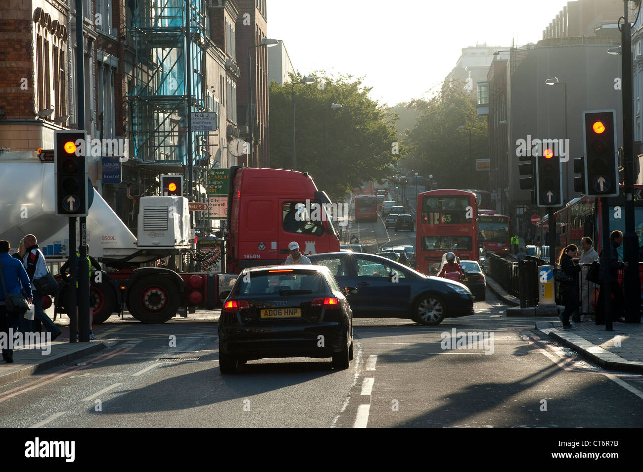 Traffic waiting at red traffic lights on a busy London street early in the morning, England. - Stock Image