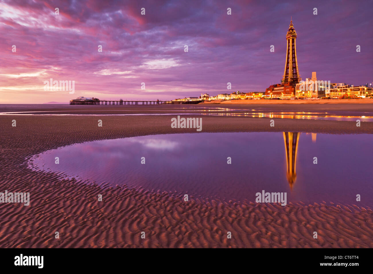 Blackpool tower reflected in a tide pool and seafront amusements illuminated at sunset Lancashire England GB UK - Stock Image