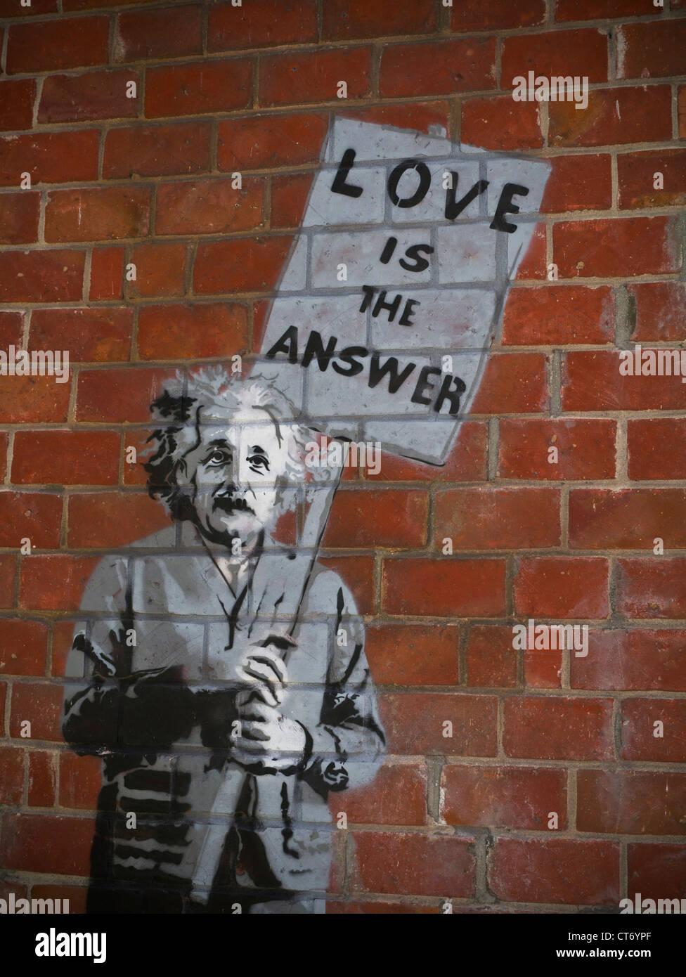 ALBERT EINSTEIN 'BANKSY' Street art on brick wall of Albert Einstein holding placard '' Love is the answer'' - Stock Image