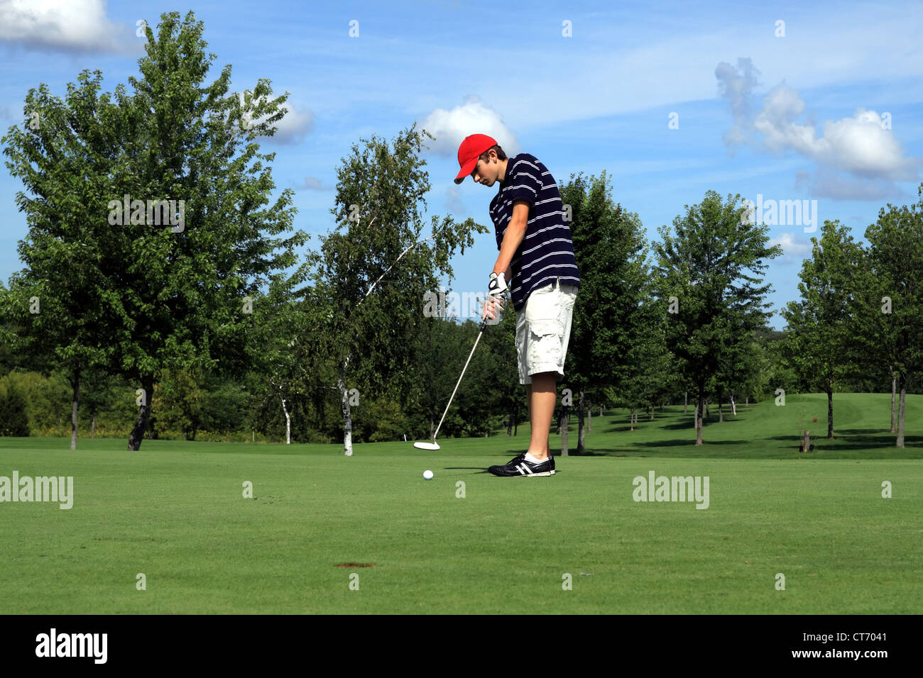 Young golfer on putting green - Stock Image