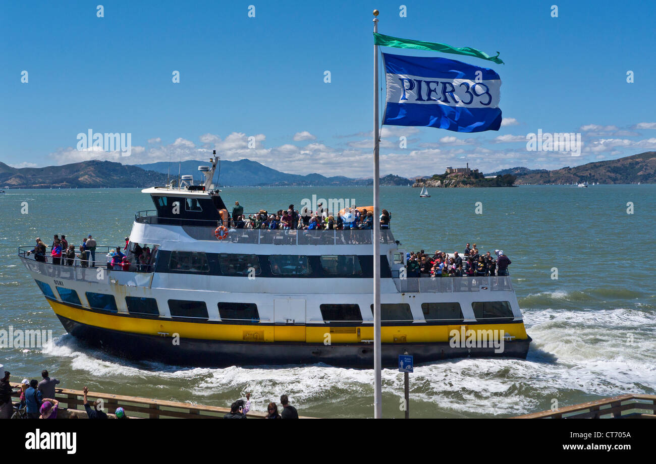 ALCATRAZ Pier 39 flag with Alcatraz prison island behind, tour boat returning from Bay cruise Embarcadero San Francisco - Stock Image