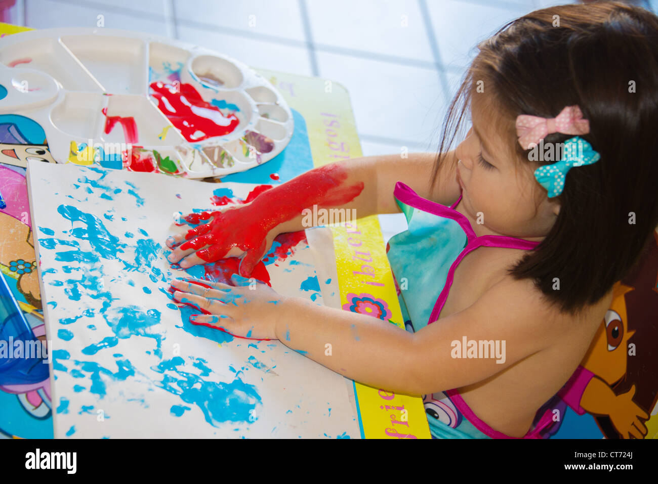 Two year old playing with paints. Stock Photo