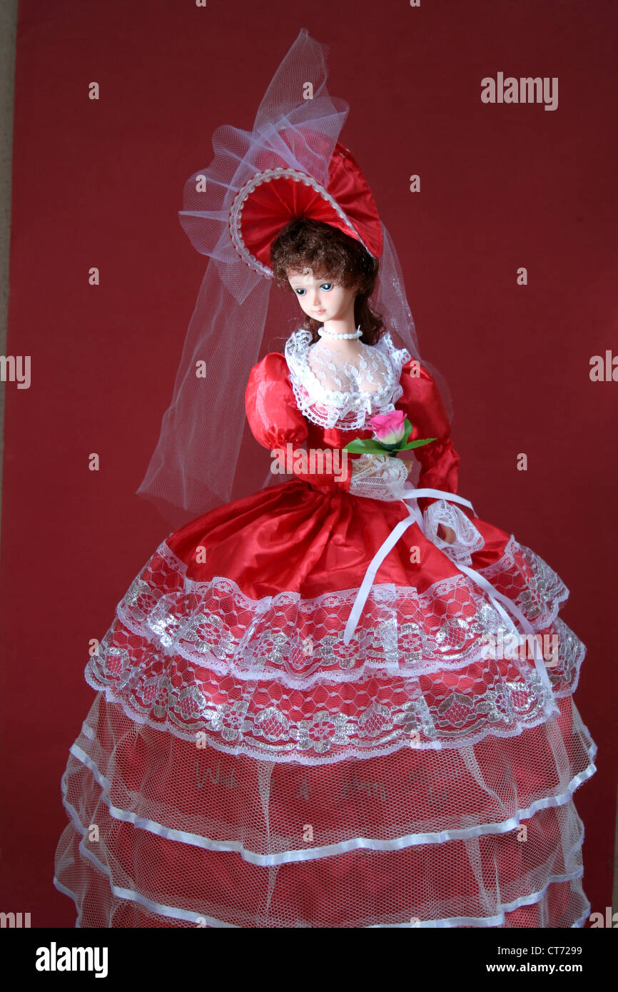 A charming and graceful doll with bright red bridal dress - Stock Image