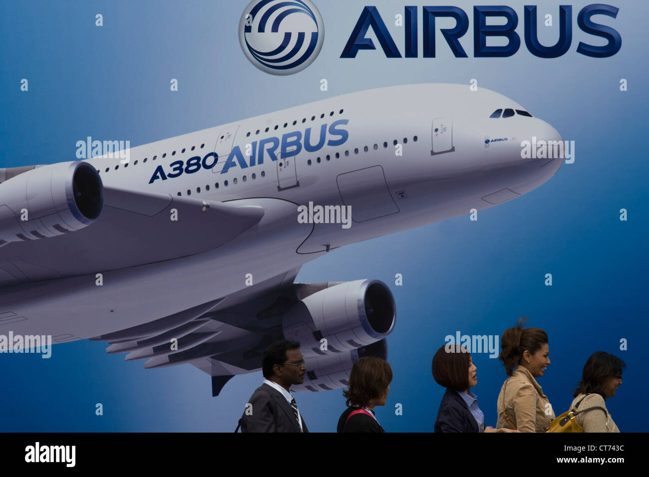 Delegates walk past a billboard of an A380 airliner outside one of the EADS company's chalets at the Farnborough - Stock Image