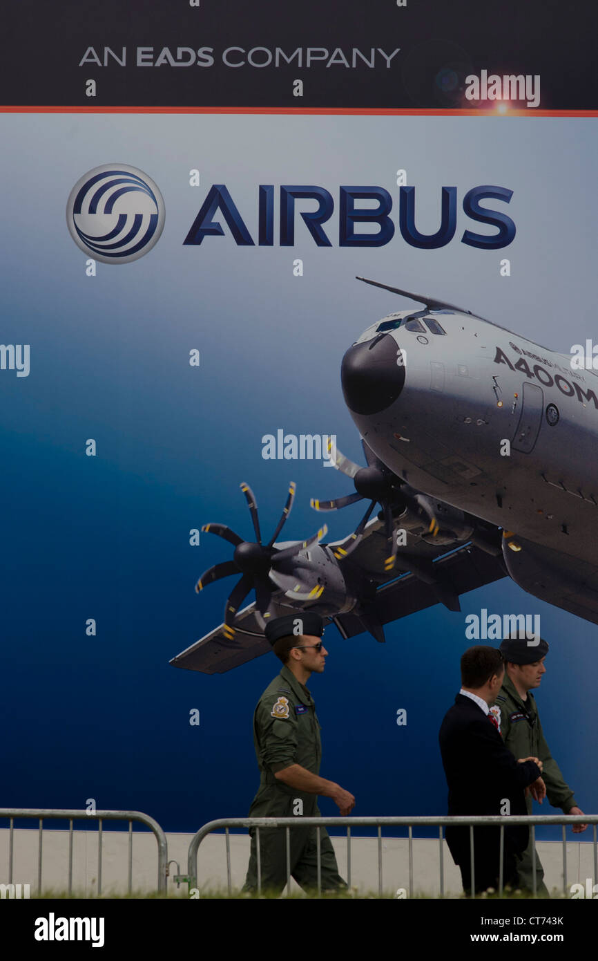 Delegates walk past a billboard of military A400M transporter outside an EADS chalet at the Farnborough Air Show Stock Photo