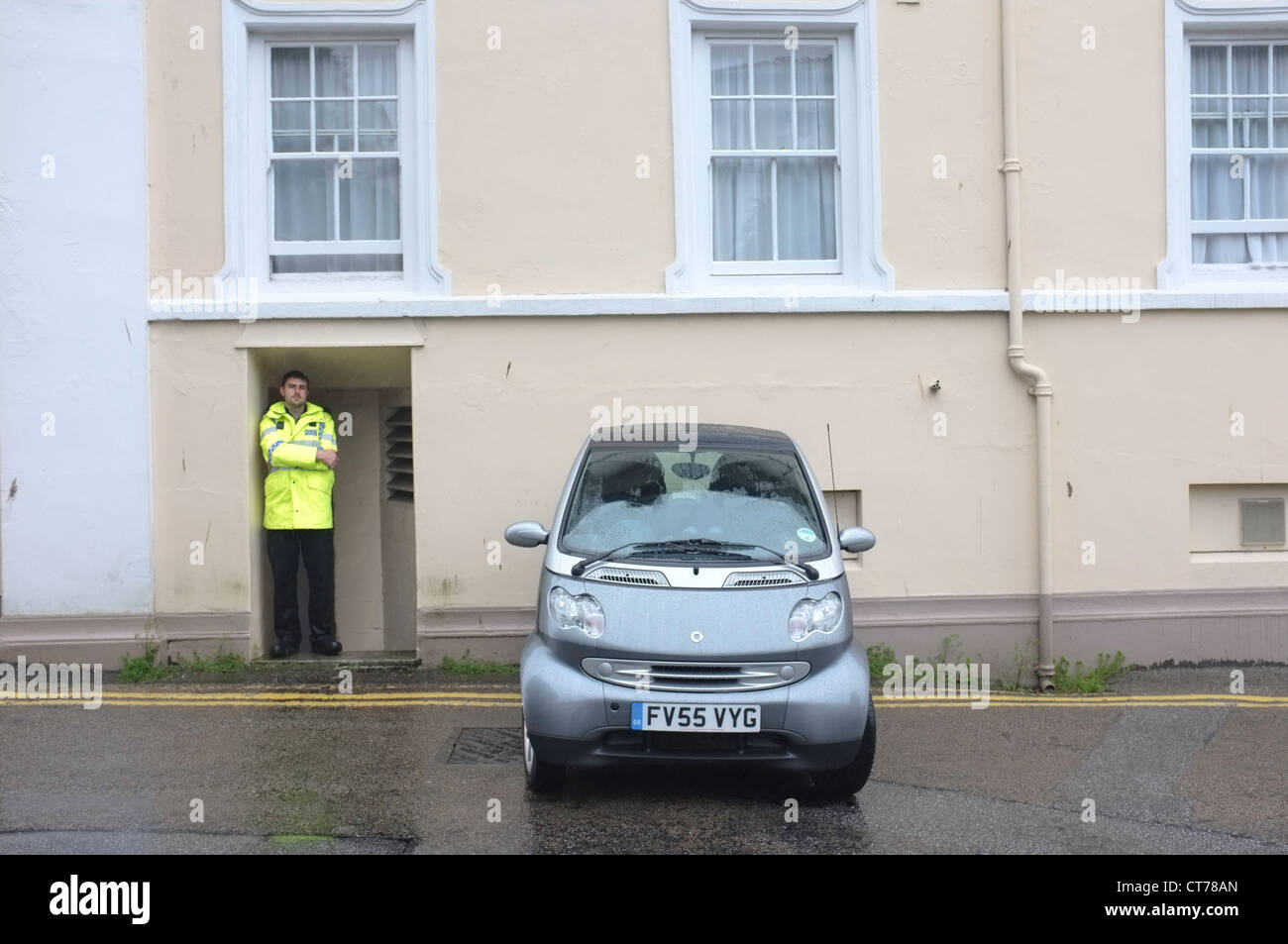 A badly parked car watched over by a policeman in Falmouth, Cornwall - Stock Image