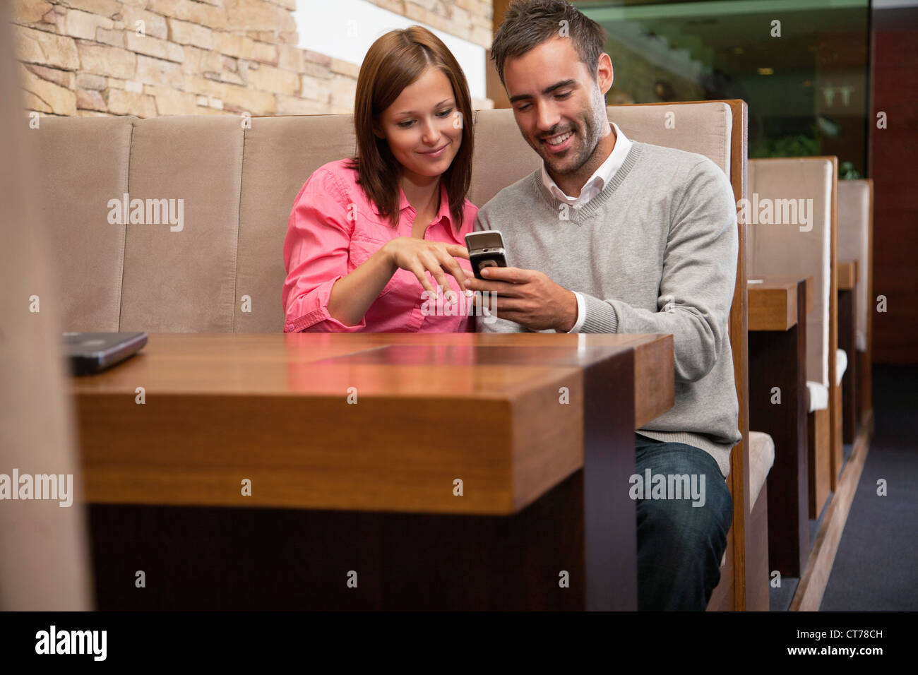 young couple looking at display of mobile phone at restaurant - Stock Image