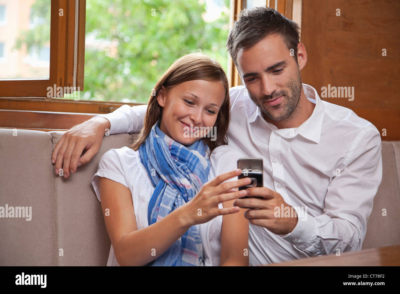 young couple looking at display of mobile phone - Stock Image