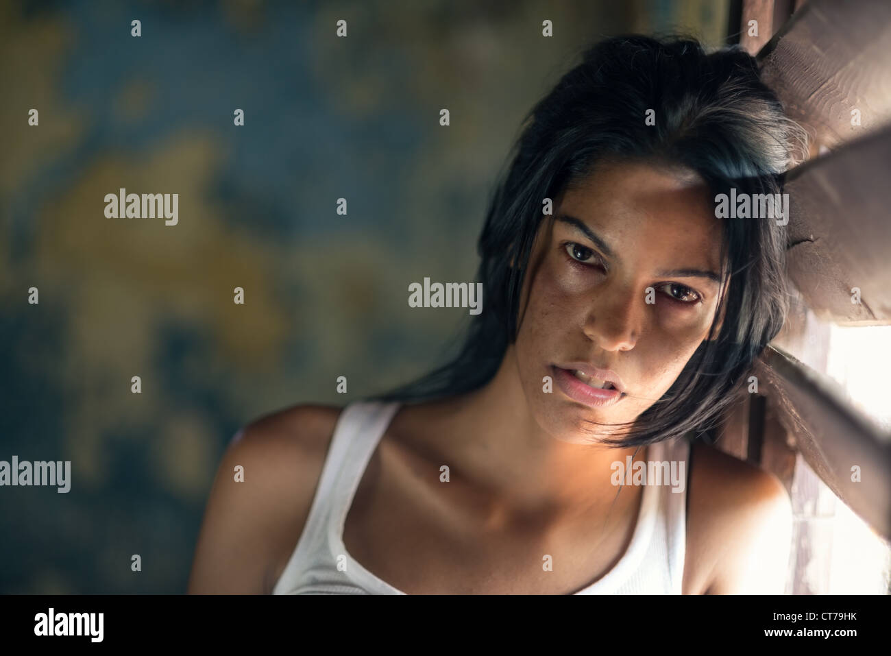 Domestic violence, portrait of abused and hurt young woman crying at home - Stock Image