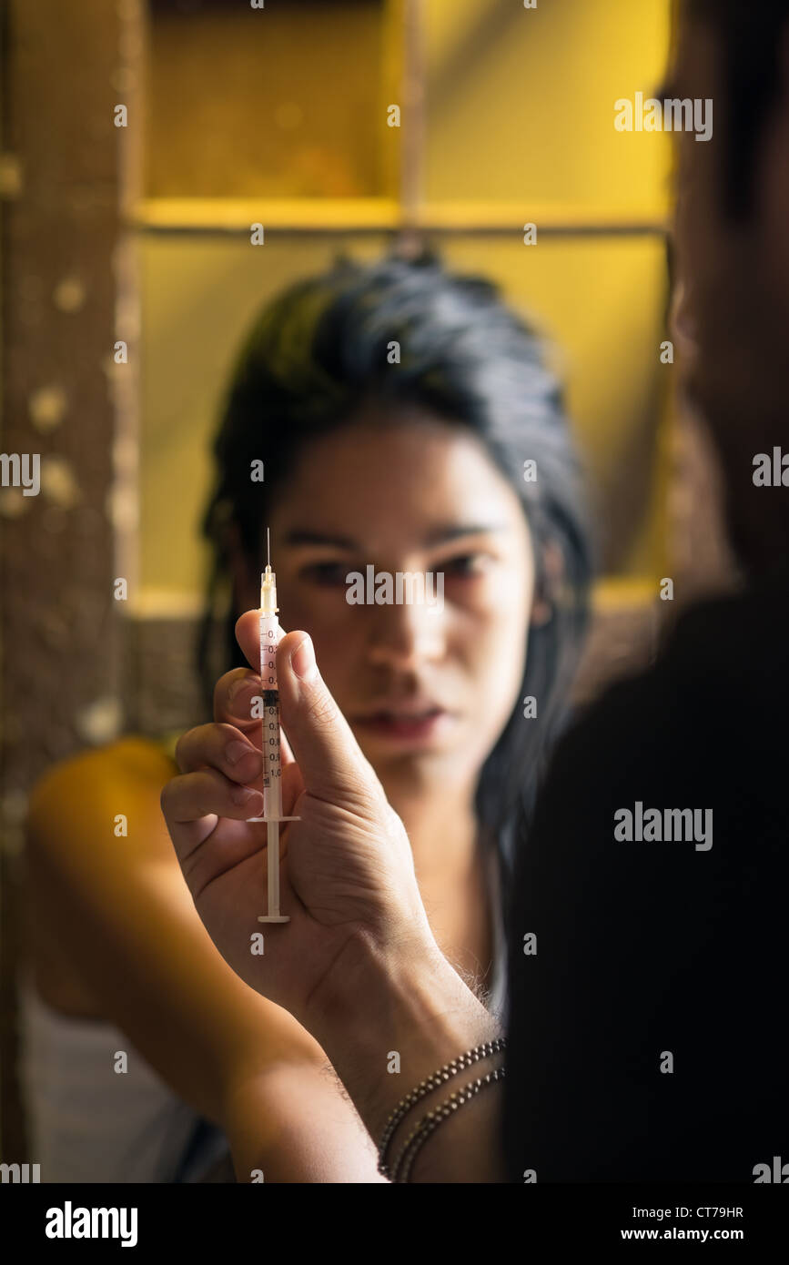 Substance abuse and people, boyfriend and girlfriend shooting up with heroin syringe - Stock Image