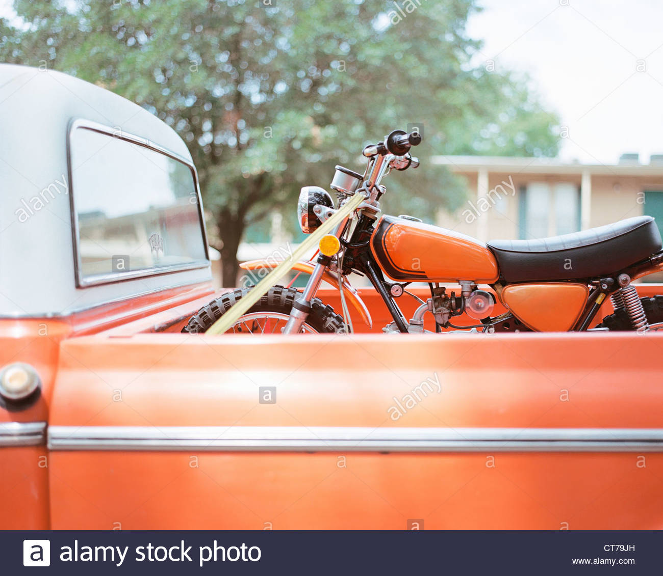 Orange motorcycle in pick up truck - Stock Image