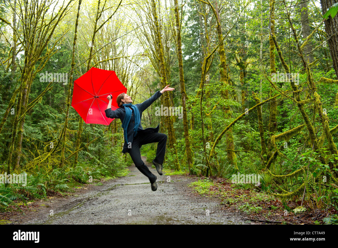 Jumping woman in forest with red umbrella Stock Photo