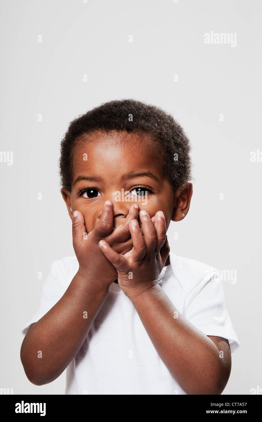 Boy covering mouth with hands Stock Photo