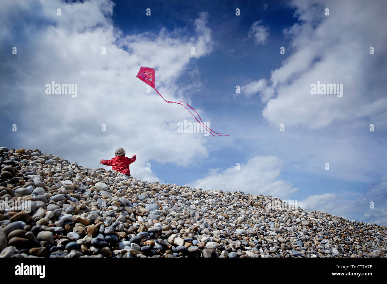 Little boy flying a kite on a pebble beach - Stock Image