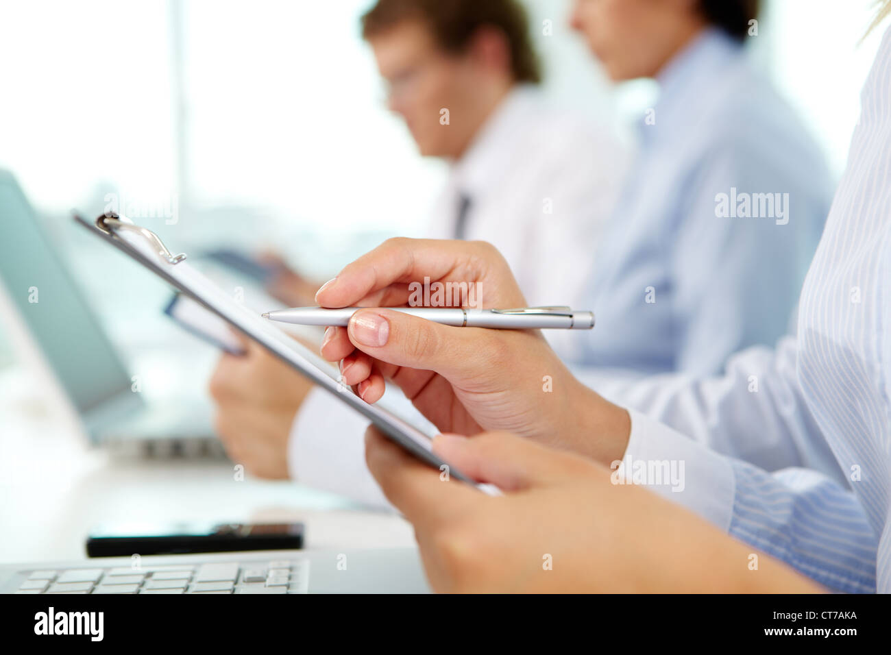 Female hands holding pen and clipboard while making notes with business partners working on background - Stock Image