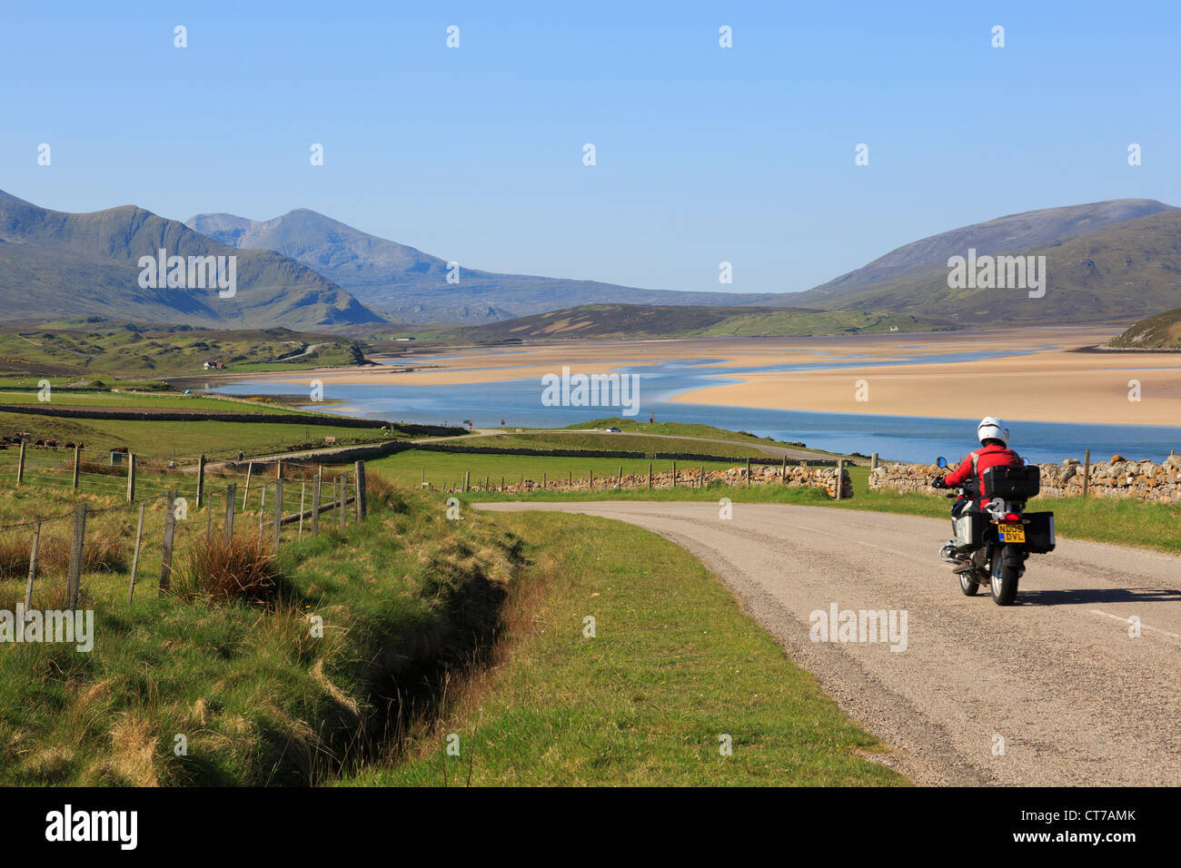 Biker riding on a bike on scenic A838 country North Coast 500 road on North and West Highlands Tourist Route in - Stock Image