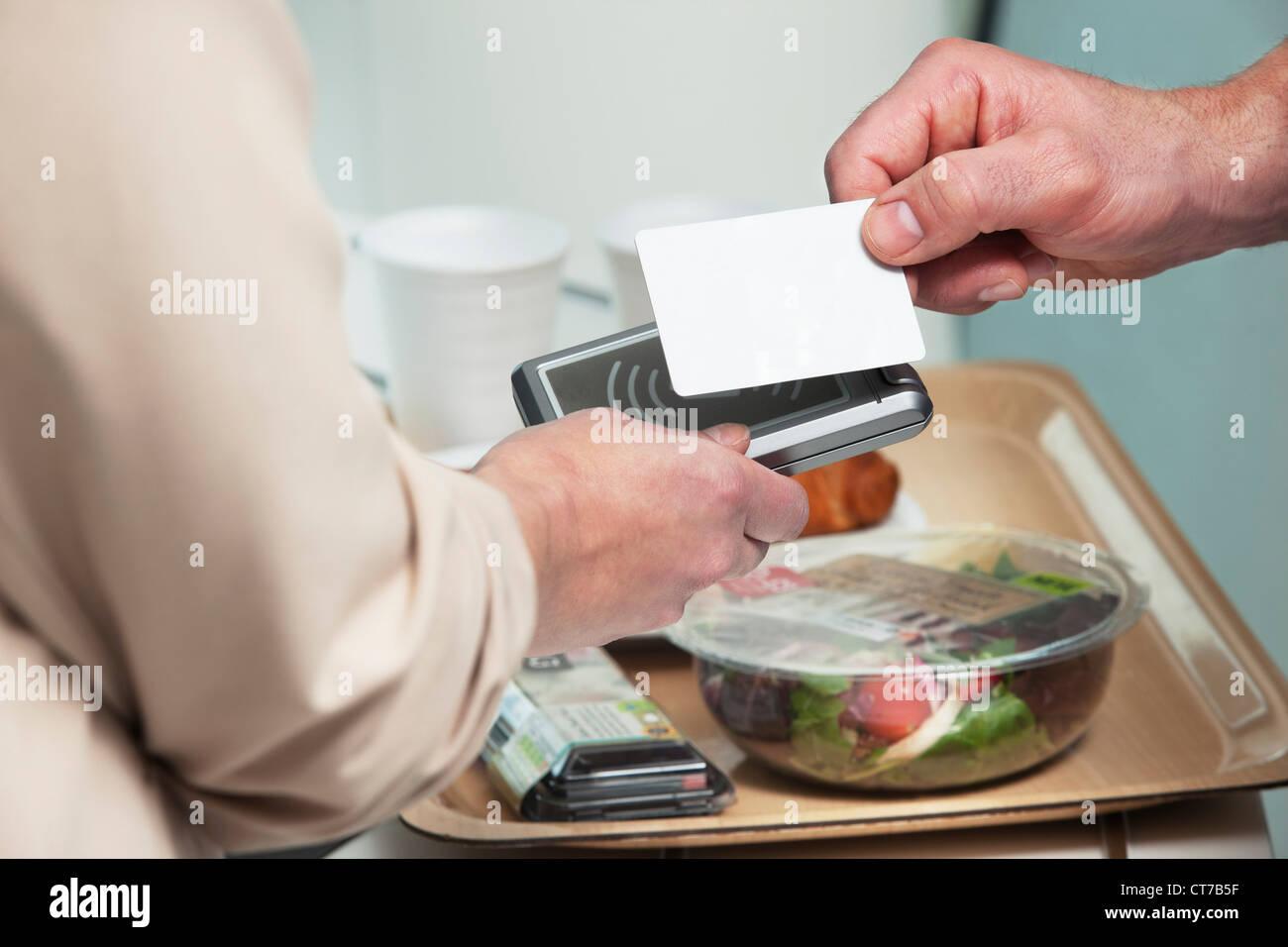 Man using card to buy food - Stock Image