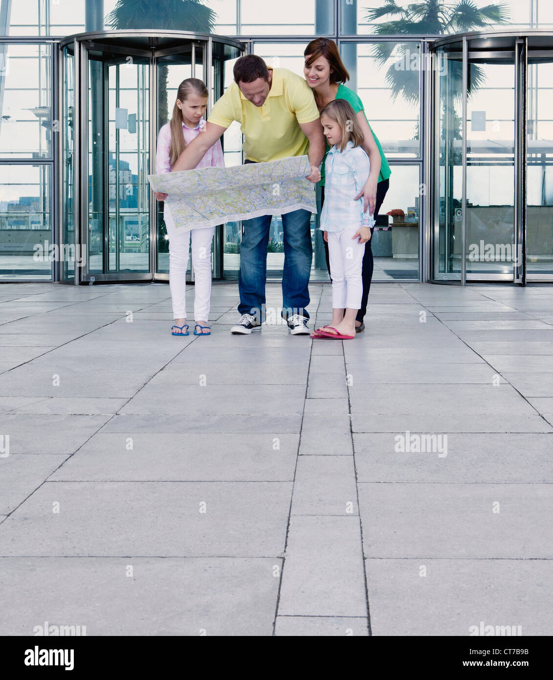 Family with map outside airport - Stock Image