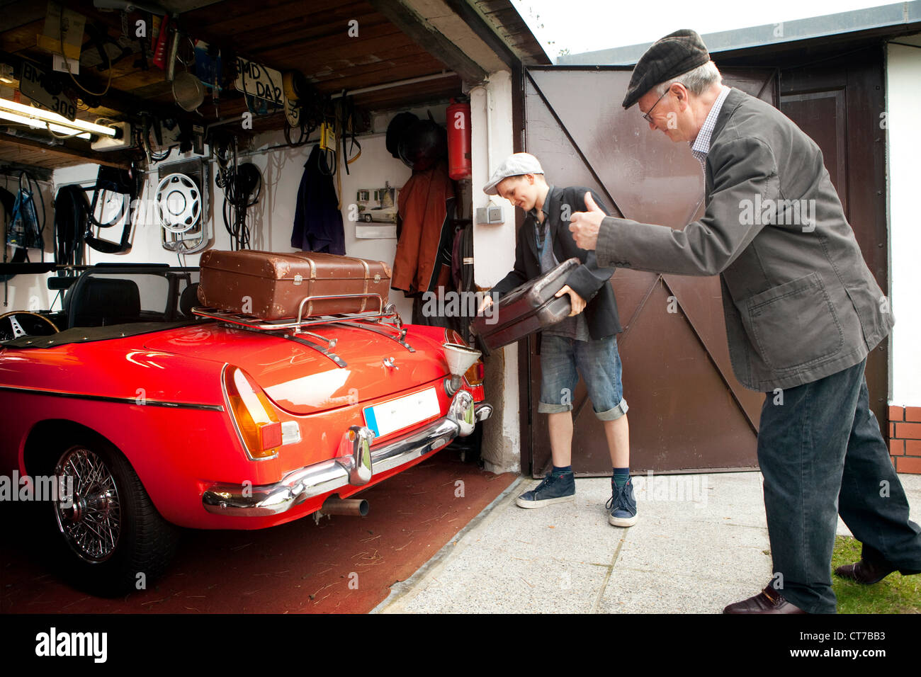 Grandfather and grandson packing vintage car with trunk suitcases in garage - Stock Image