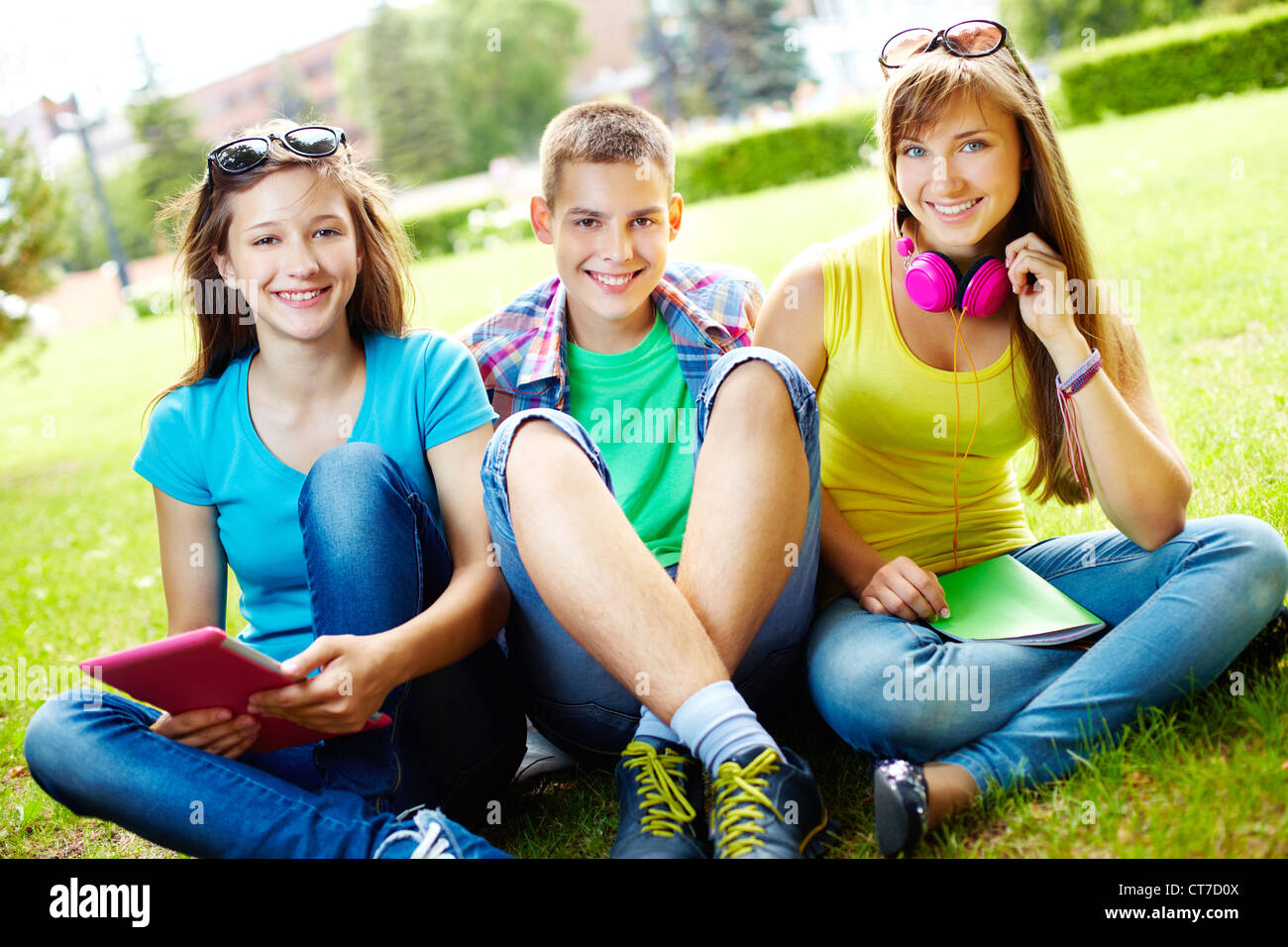 Portrait of three college students enjoying their free time outdoors - Stock Image