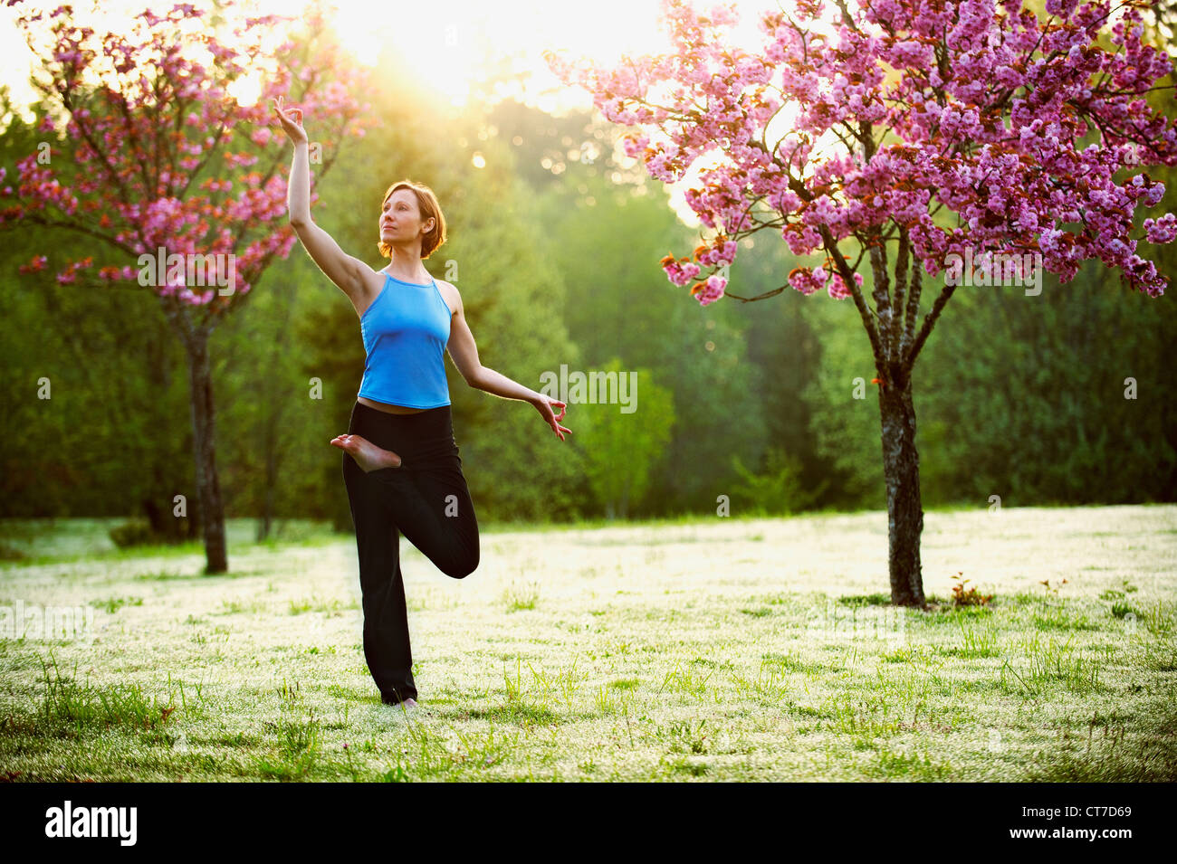 Woman in yoga pose in park - Stock Image