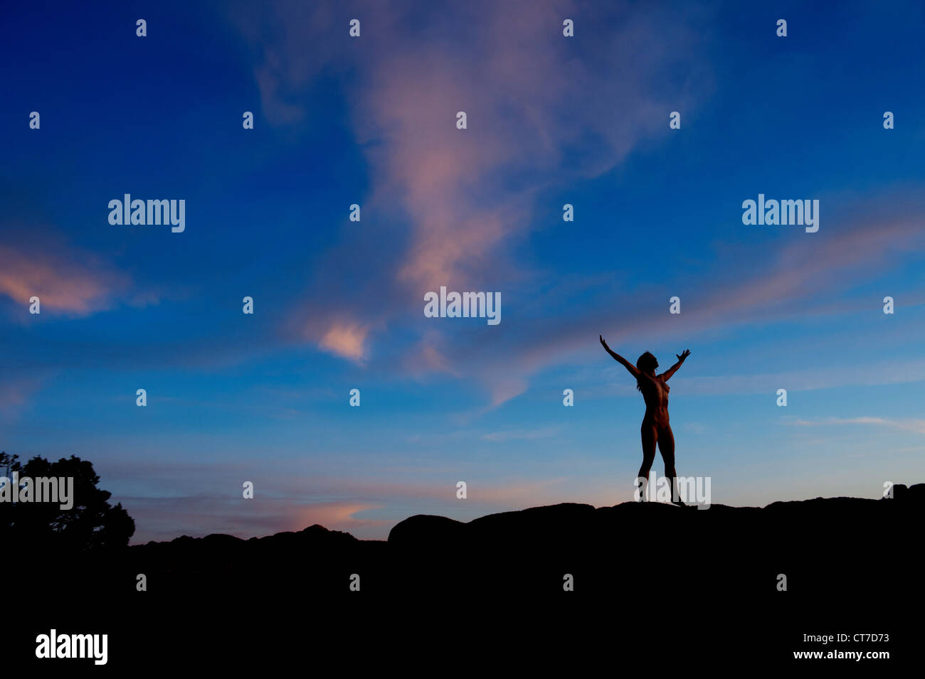 Young woman standing in desert with arms open, silhouette - Stock Image