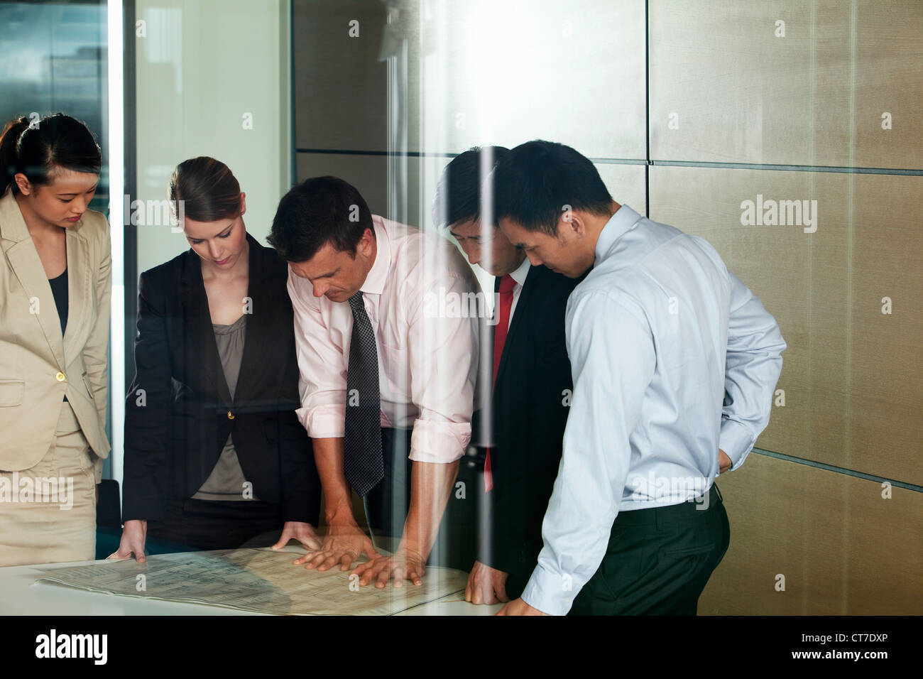 Multi racial businesspeople discussing blueprint - Stock Image