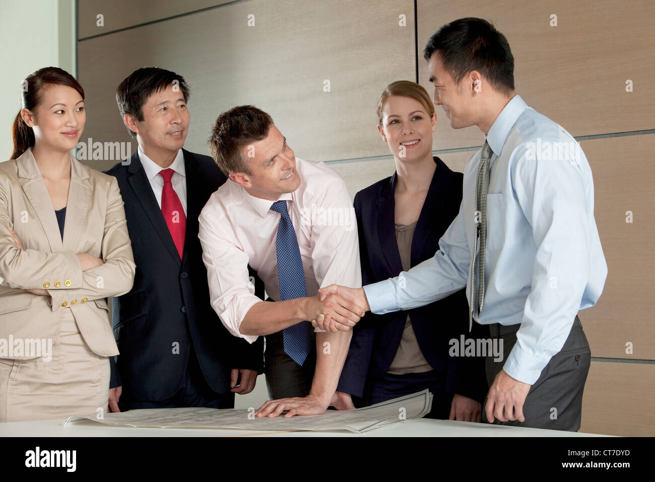 Multi racial businesspeople shaking hands over blueprint - Stock Image