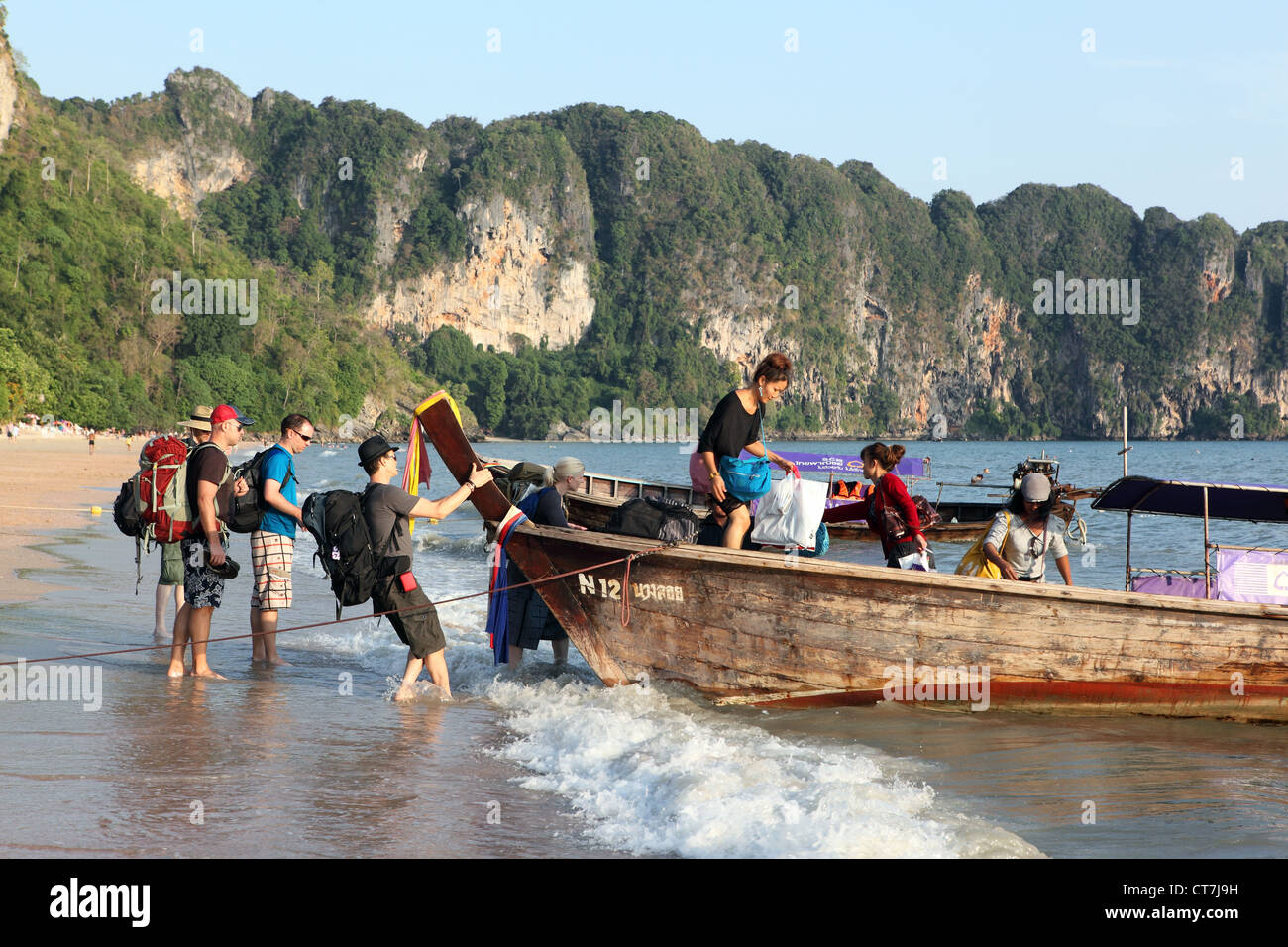 Tourists getting onto a long tail wooden boat at Ao Nang Beach in Krabi, Thailand Stock Photo