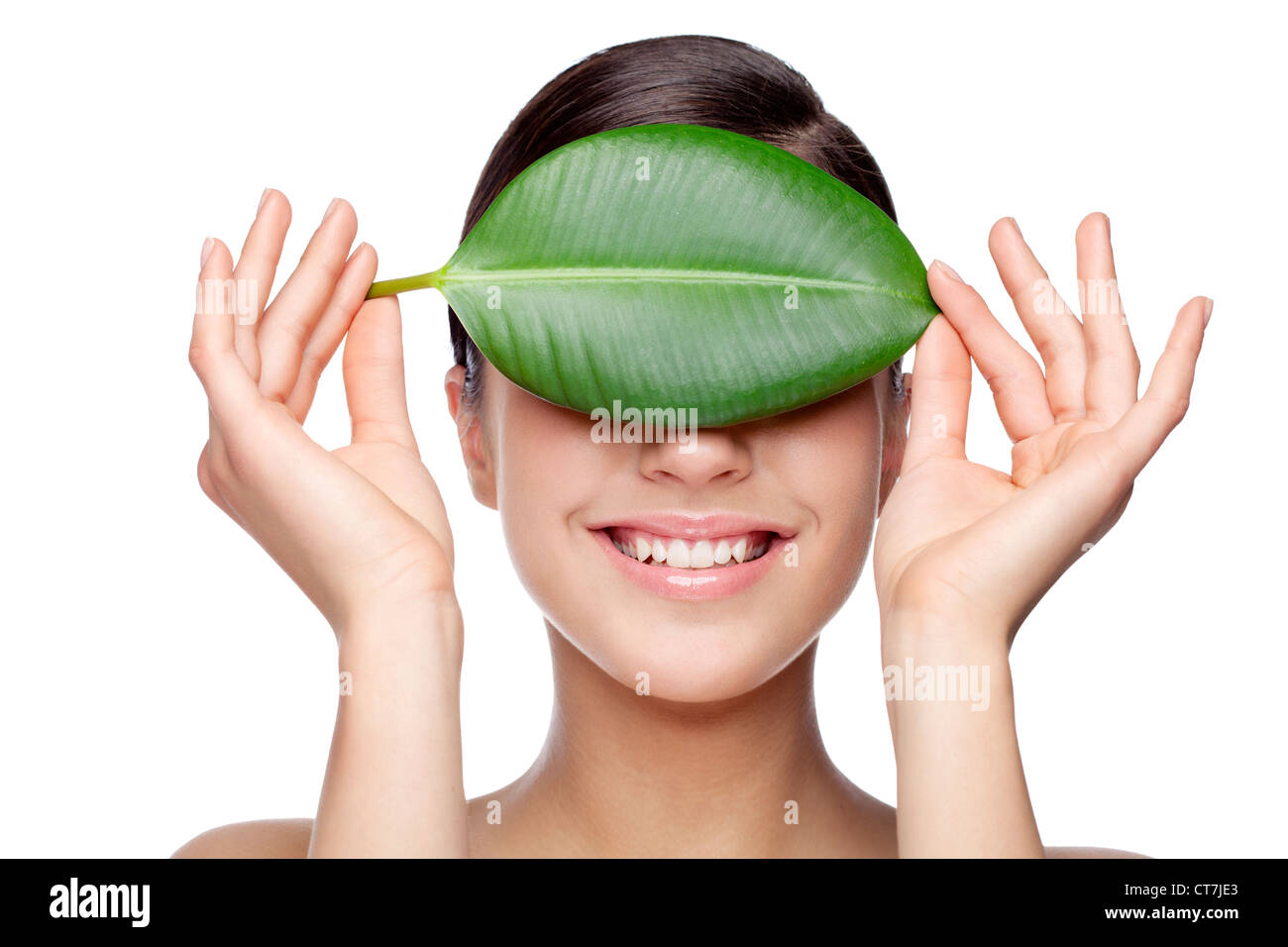 smiling female hiding behind green leaf - Stock Image