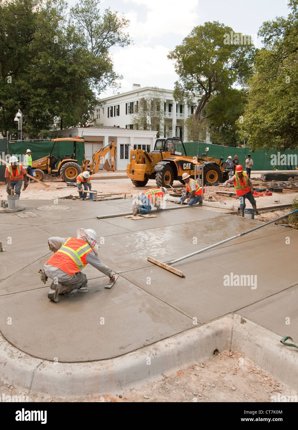 Hispanic male concrete workers complete concrete sidewalk in front of newly renovated Texas Governor's Mansion - Stock Image