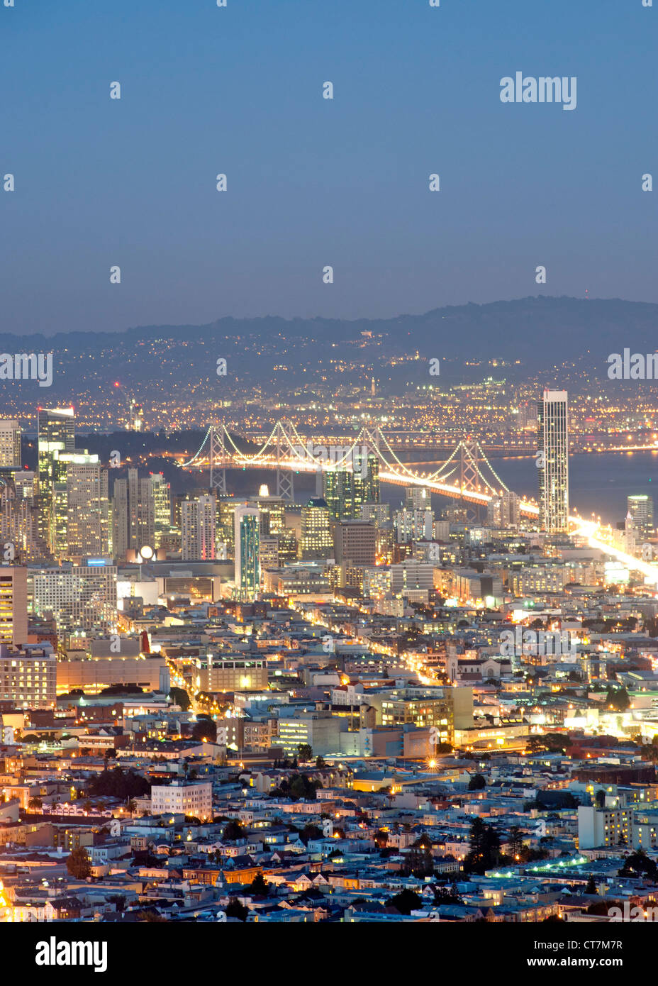Dusk view across San Francisco and the Oakland Bay Bridge from the summit of Twin Peaks in California, USA. - Stock Image