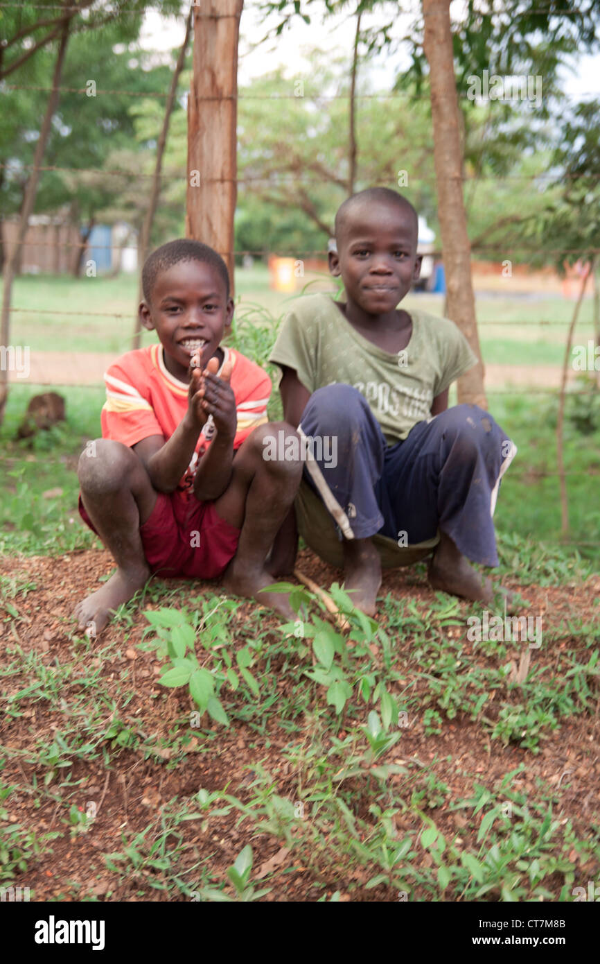 Two young Kenyan boys sit by the road side. Stock Photo