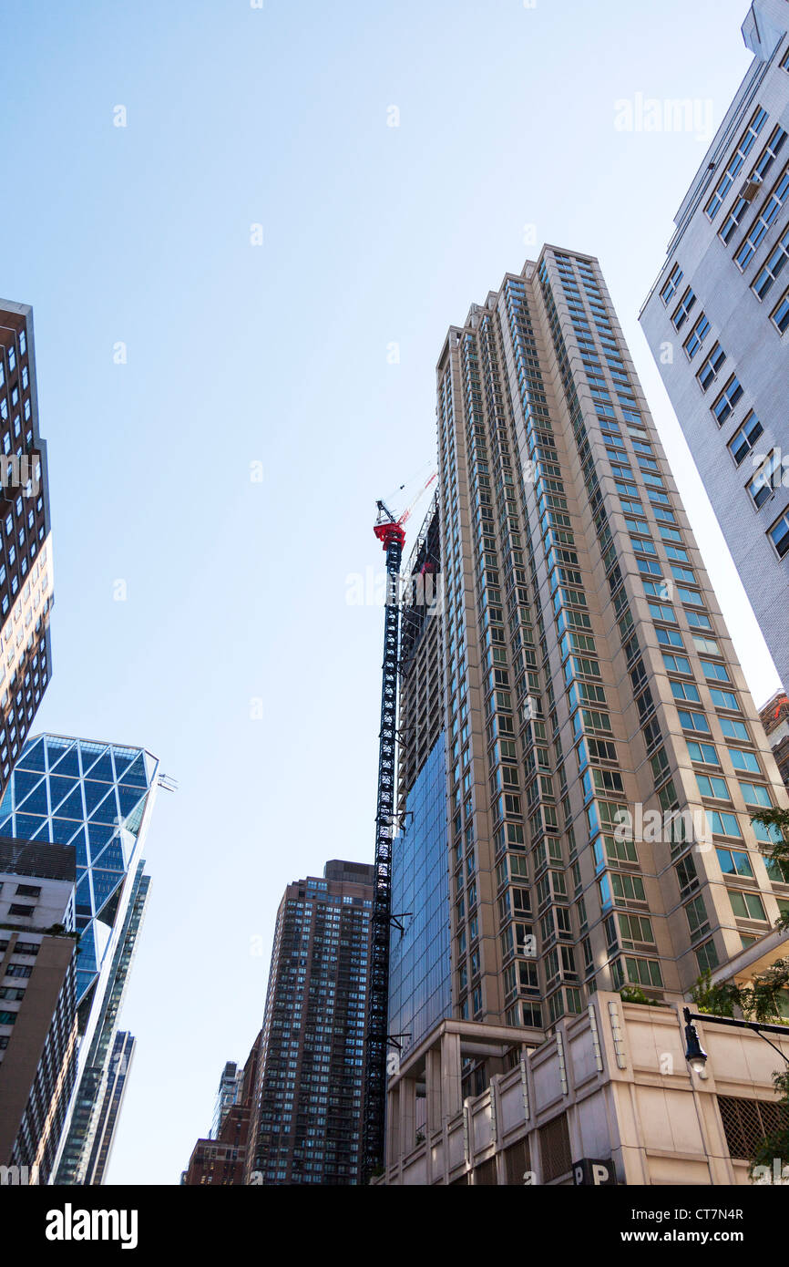 Huge skyscraper being worked on with large tallest tower cranes, used for constructing high buildings - Stock Image