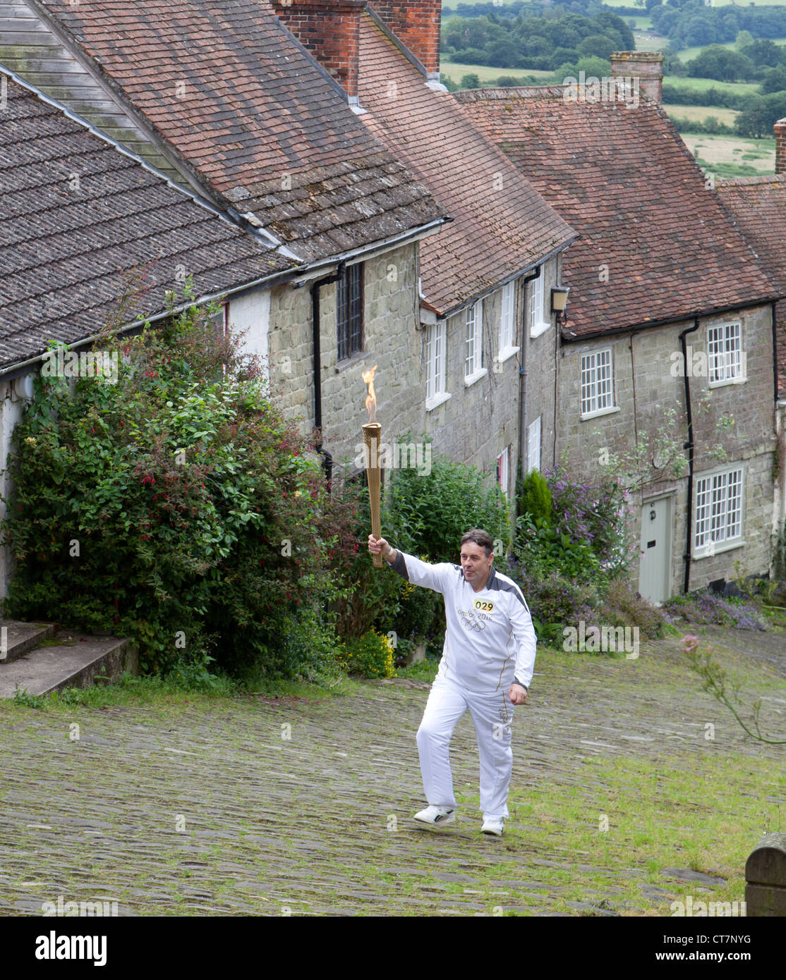 Pictured on Gold Hill is Alan Surtees MBE who arrived in Shaftesbury carrying the torch. - Stock Image