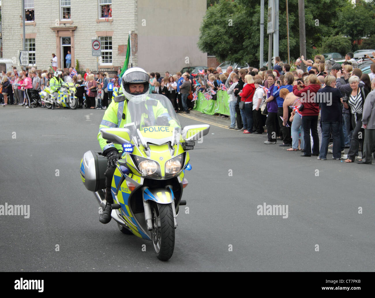 a UK police motorcycle outrider and crowds of people - Stock Image