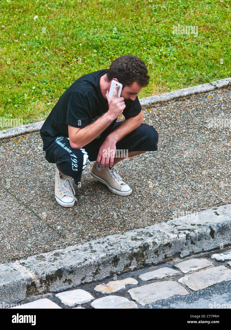 Younger man with telephone crouching on pavement - France. - Stock Image
