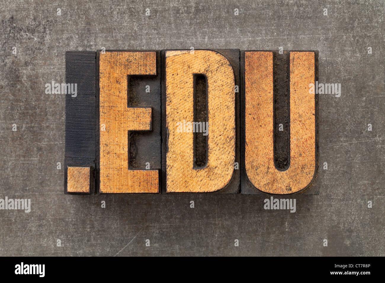 dot edu - internet domain for education in vintage wooden letterpress printing blocks on a grunge metal sheet - Stock Image
