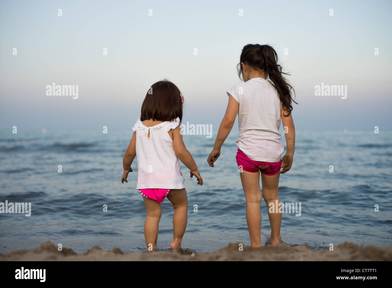Two girls on a beach looking out across open water. - Stock Image