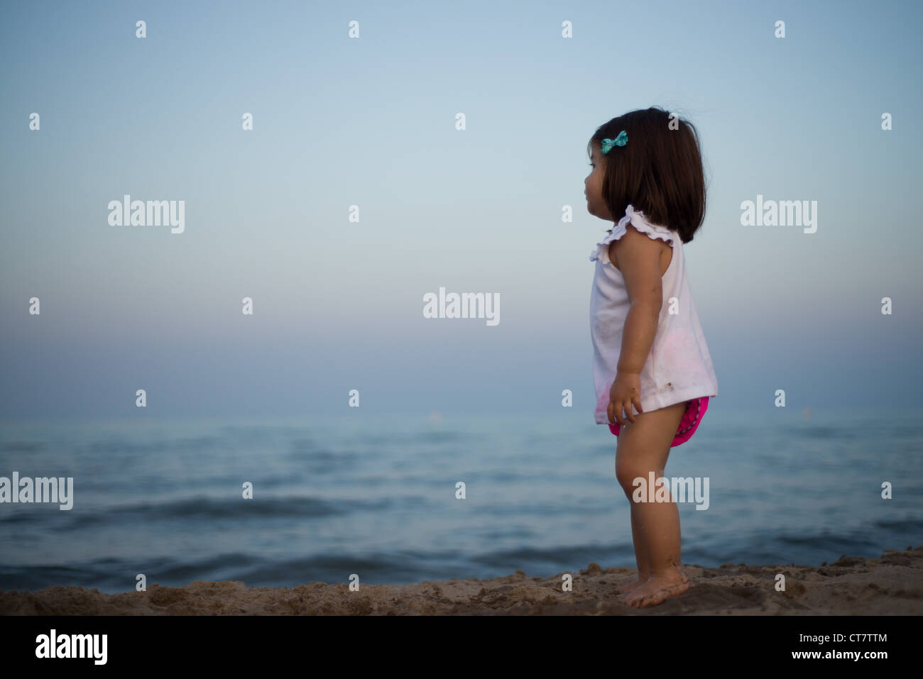 Young girl looking out across open water Stock Photo