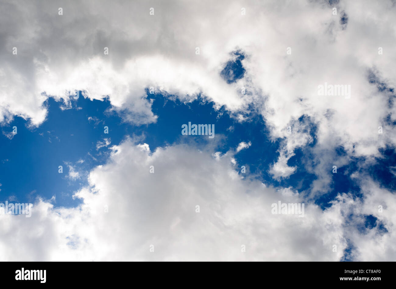 Fluffy clouds in a blue sky sky - Stock Image