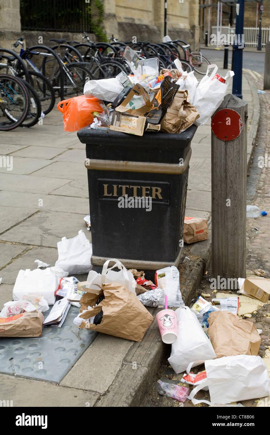 overflowing litter bin on city street - Stock Image