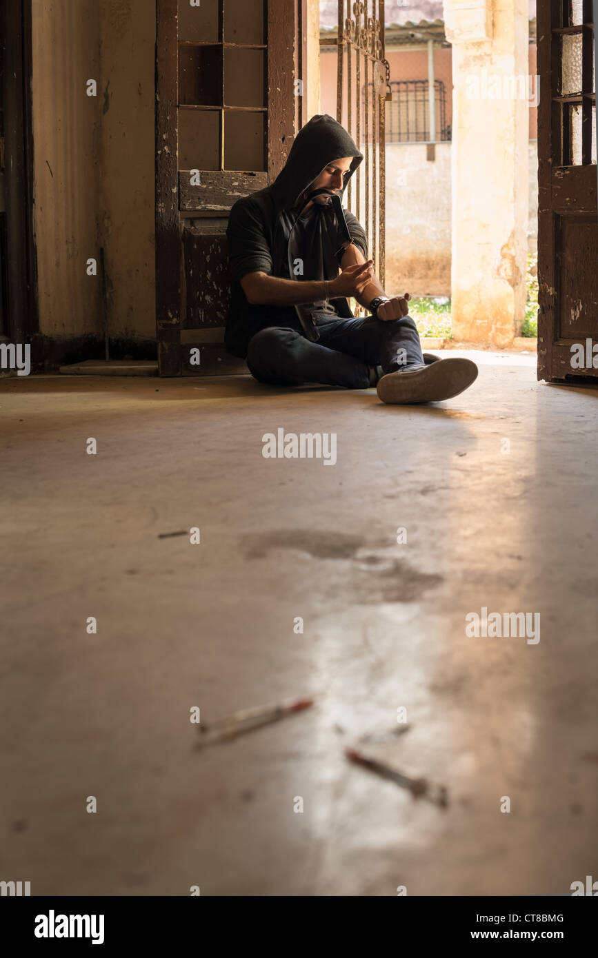 Heroin junkie shooting up drugs with syringe. Low angle view, copy space - Stock Image