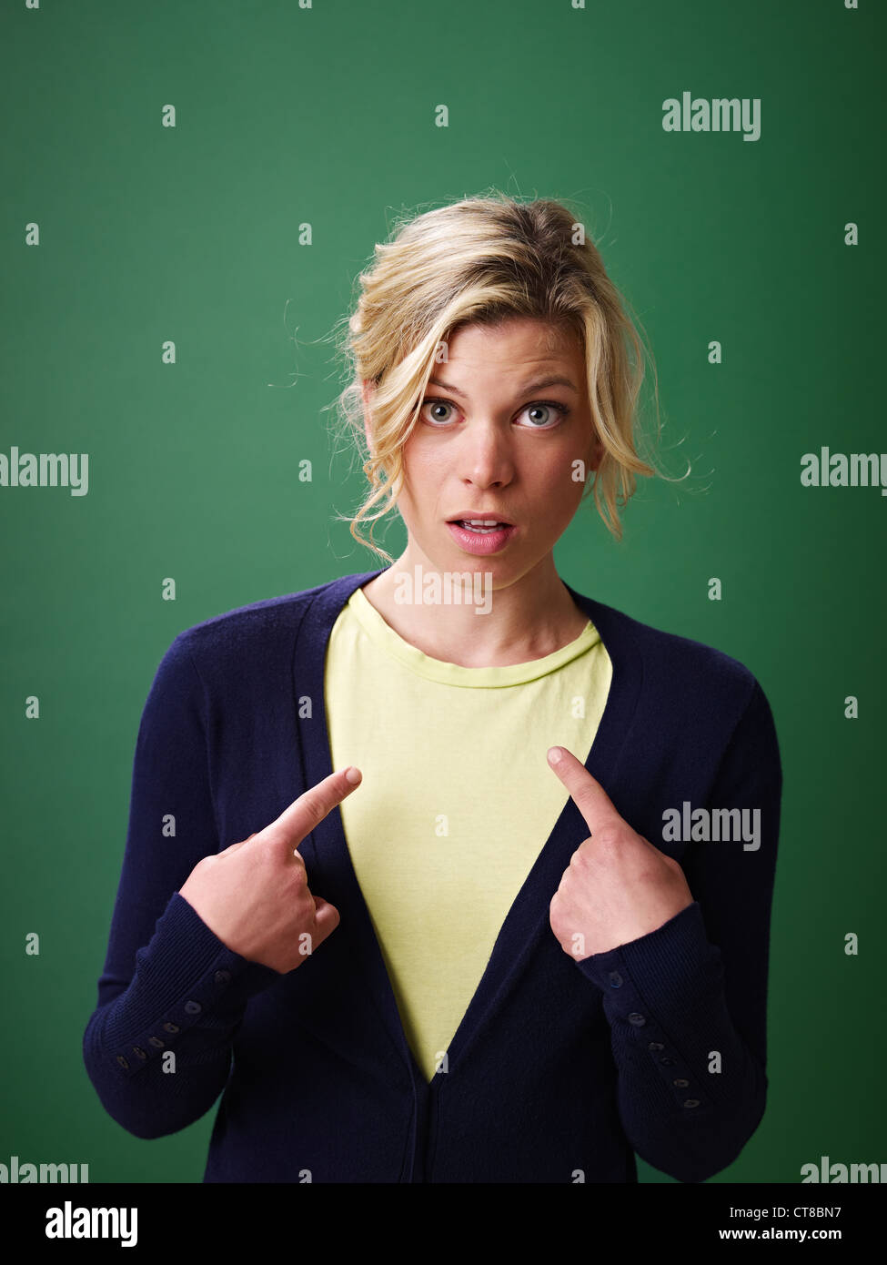 young woman pointing at herself against green background and looking at camera - Stock Image