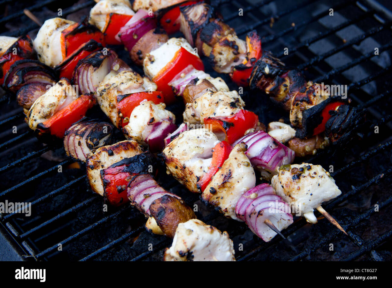 cooked chicken and vegetable kebabs on a barbecue - Stock Image