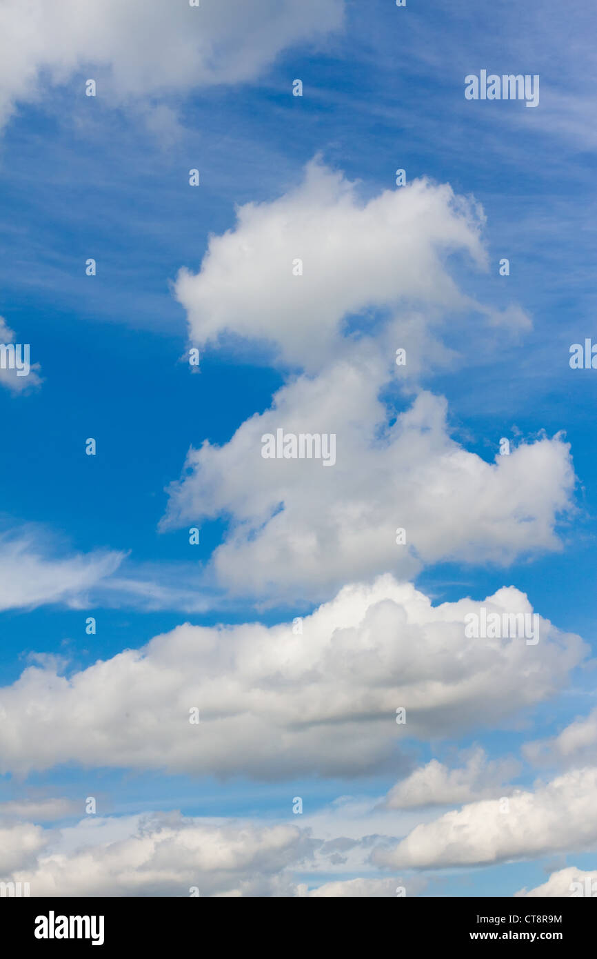 white wispy clouds in a vibrant blue sky - Stock Image