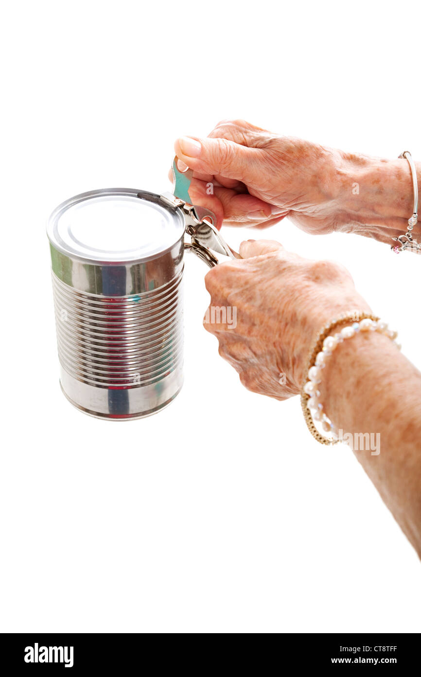 Closeup of elderly hands, with arthritis, struggling to use a can opener. Isolated on white.  - Stock Image