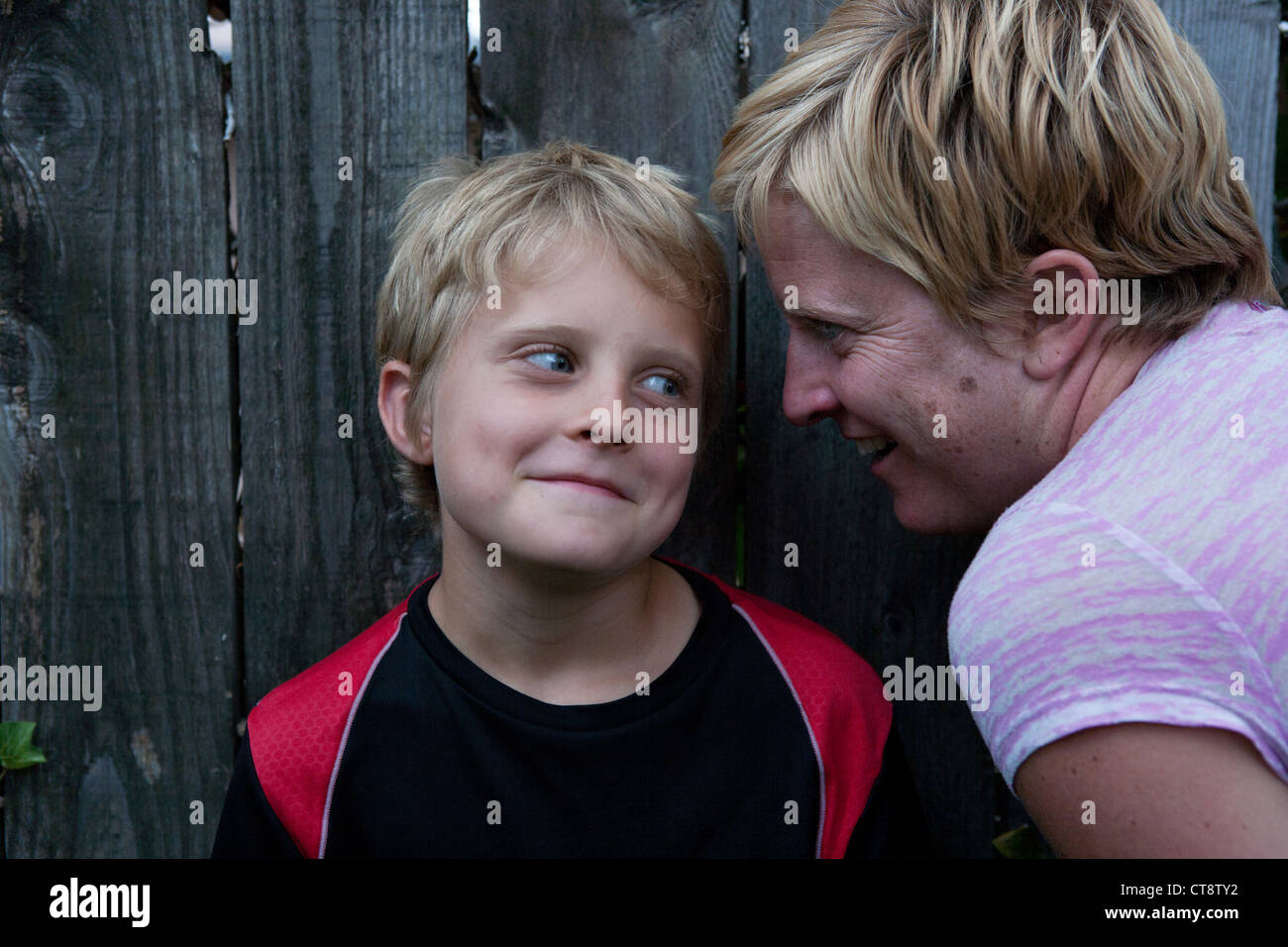Mom whispering something in her son's ear and boy smiling. Stock Photo