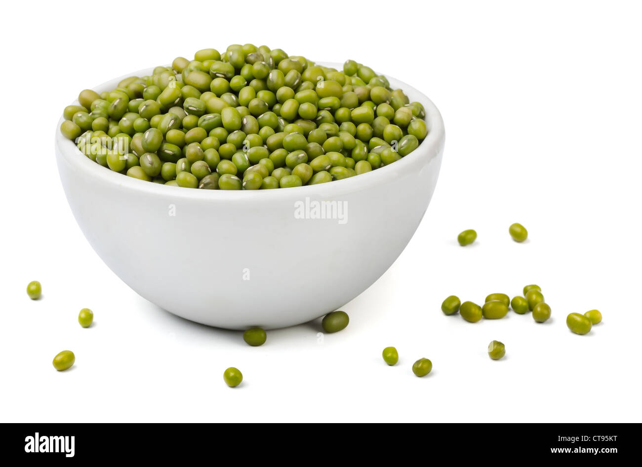 Green mung beans in white bowl isolated on white - Stock Image